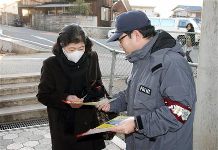 A policeman handing out flyers about the Sunami murders.